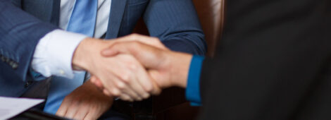 Closeup of two smiling business men shaking hands in cafe. One man is sitting back to camera.